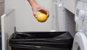 woman putting moldy lemon in the garbage can